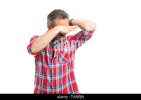 Man with disgusted expression holding nose as smelling sweaty armpit isolated on white background - Stock Image