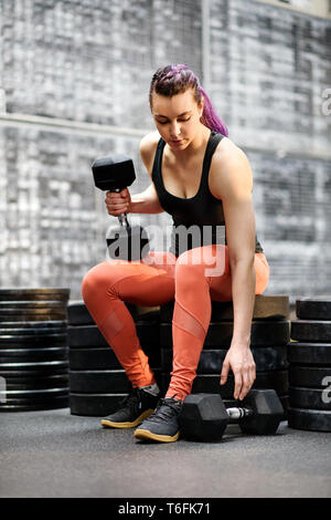 Fit muscular young woman athlete at the gym reaching down to pick up a large dumbbell weight before commencing body building or weight lifting exercis - Stock Image