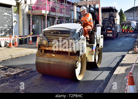 Road roller working on refurbishment of city street with fresh tarmac, England, UK - Stock Image