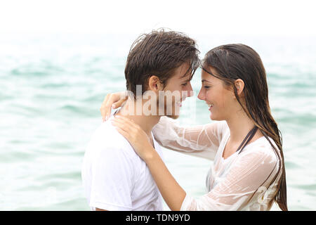Happy couple ready to kiss bathing on the beach on summer vacation - Stock Image