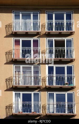 Die Geländer von kleinen Balkonen eines Mehrfamilienhauses werfen Schatten. - Stock Image