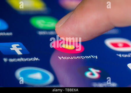 Finger pressing a shortcut icon on a smartphone or tablet touchscreen to load the Houseparty social media app. House party application. - Stock Image