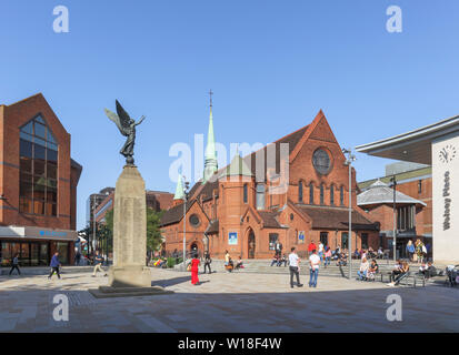Christ Church and war memorial in Jubilee Square in Woking, Surrey, south-east England on a sunny summer day, clear blue sky - Stock Image