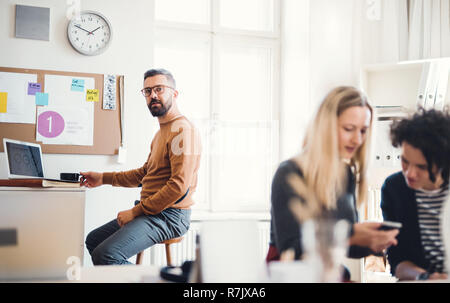 Group of young, cheerful, male and female businesspeople with smartphone and laptop working together in a modern office. - Stock Image