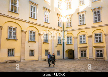 View of a middle aged couple walking through the Schweizerhof (Swiss Courtyard) in the Hofburg palace complex in Vienna, Wien, Austria. - Stock Image