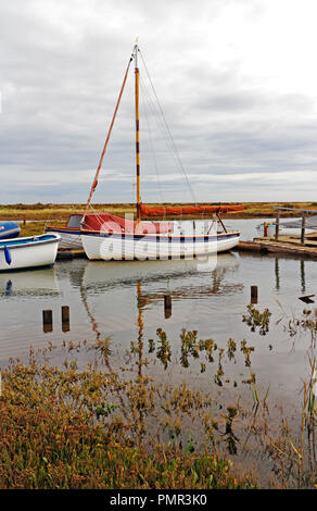 A yacht with reflection moored in Morston Creek during a flood tide in North Norfolk at Morston, Norfolk, England, United Kingdom, Europe. - Stock Image