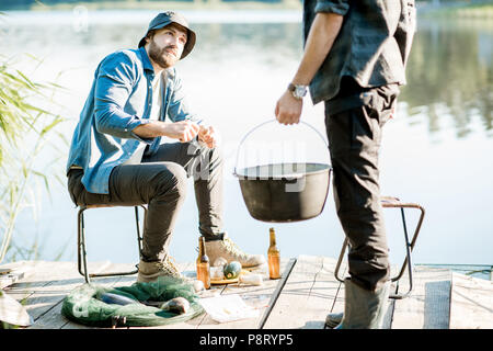 Two fishermen preparing some food during the picnic on the wooden pier near the lake in the morning - Stock Image