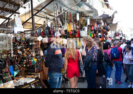 Male stall owner looks at camera in Florence San Lorenzo market, with ladies shopping nearby,Tuscany,Italy - Stock Image
