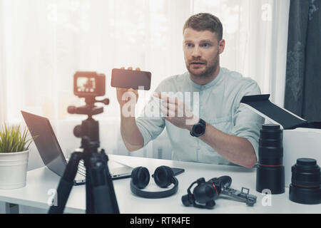 technology blogger recording new smart phone review - Stock Image