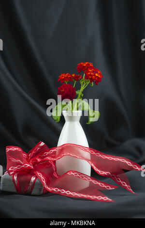 Special gift wrapped with red ribbon placed with red lantana flowers in white vase against black satin background has joyful mood of romance and celeb - Stock Image