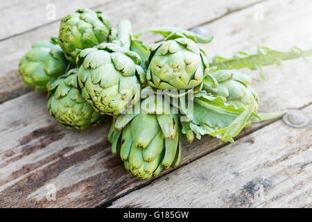 Artichokes on wooden floor - Stock Image