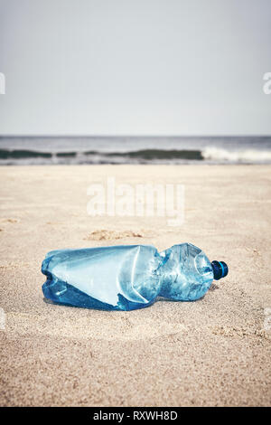 Empty plastic bottle on a beach, selective focus, color toning applied. - Stock Image