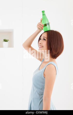 Young woman holding water bottle and looking up with smile, - Stock Image