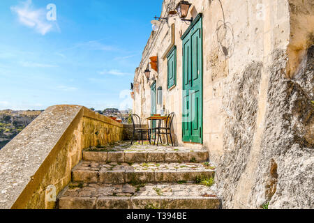 Two chairs and a table with a bottle of wine sit on a small deck outside a green door and shutter in the ancient city of Matera, Italy. - Stock Image