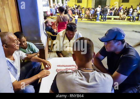 Cartagena Colombia Old Walled City Center centre Getsemani neighborhood night nightlife Hispanic resident residents man friends playing game dominoes - Stock Image