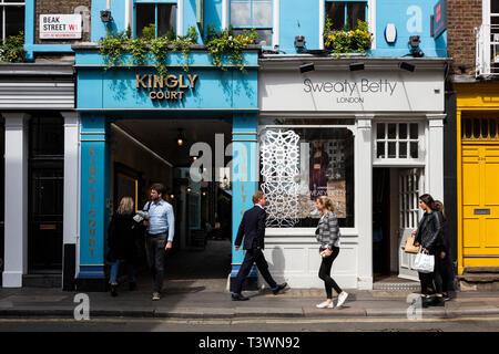 People walking down Beak Street with Kingly Court in Soho, London, England, United Kingdom, Europe - Stock Image