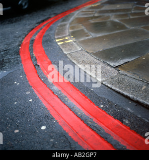Double red lines on a bend in a road London UK  KATHY DEWITT - Stock Image