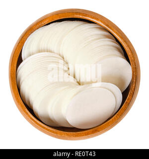 Round white wafer papers for baking in wooden bowl. Thin sheets, made of wheat flour and starch, for making cookies. Edible. Isolated macro food photo - Stock Image
