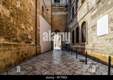 A woman stands under a medieval bell tower tunnel that opens up to the ancient Piazza del duomo in the historic center of Brindisi Italy. - Stock Image
