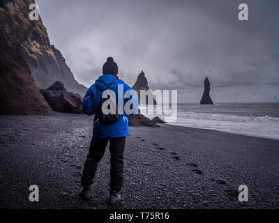 Rear view of man on wet sand near rough stony cliffs on stormy day on Reynisfjara Black Beach in Iceland - Stock Image