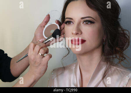 Make-up artist working in make-up studio, applies a make-up brush to face. Female face close up. - Stock Image