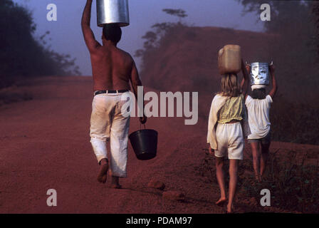 Settler family, father and children carry buckets of water at Transamazonica road, Para State, Amazon, north Brazil. - Stock Image