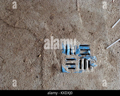 Metal grid of water drain system hole in concrete floor of barn - Stock Image