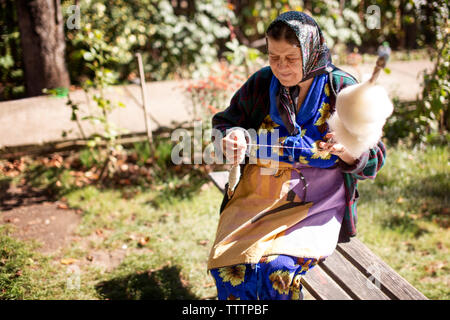 Senior woman spinning cotton thread while sitting on bench at yard - Stock Image