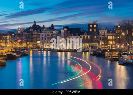 Beautiful Amsterdam canal with light trails of passing canal boat. - Stock Image