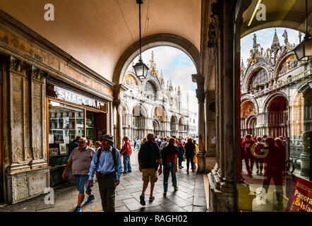 Tourists pass through the tunnel under the clock tower and onto St. Mark's Square and the Basilica in Venice, Italy - Stock Image