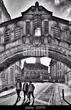 """Three friends walk underneath the famous """"Bridge Of Sighs"""" in Oxford, England. The famous Hertford Bridge landmark links the Old & New Quadrangles Of Hertford College. Photo Credit - © COLIN HOSKINS. - Stock Image"""