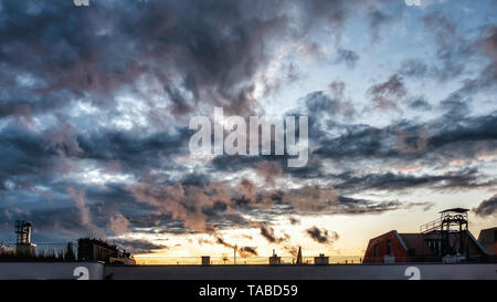 Dramatic cloudy evening sky over an apartment building rooftop at sunset in Mitte, Berlin - Stock Image