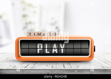 Time to play message on a retro alarm clock standing on a wooden table in a bright room - Stock Image