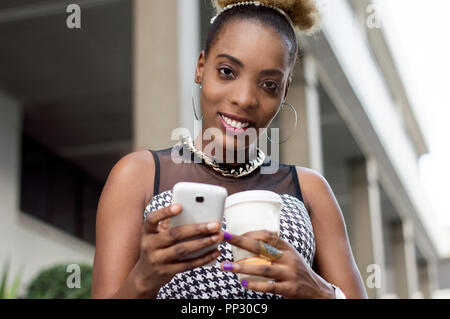 Smiling businesswoman looks at her cell phone and holds a bowl of milk. - Stock Image