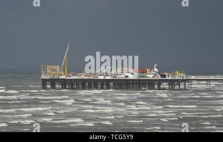 Brighton, UK. 8th June 2019.  Brighton Palace Pier with dark clouds overhead today as Storm Miguel passes through Britain bringing wet and windy conditions . Credit: Simon Dack / Alamy Live News - Stock Image