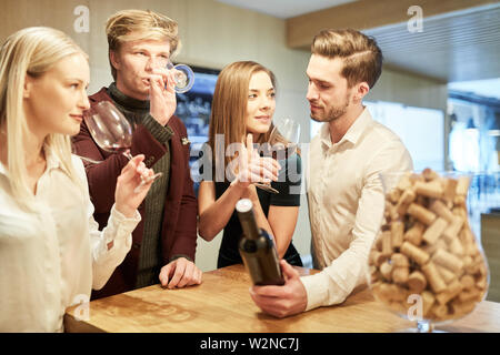 Group of young people at a wine tasting tasting red wine in the wine shop - Stock Image