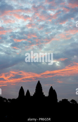 Silhouette of ruins at sunrise in Angkor Wat. The Angkor Wat complex, Built during the Khmer Empire age, located in Siem Reap, Cambodia, is the larges - Stock Image