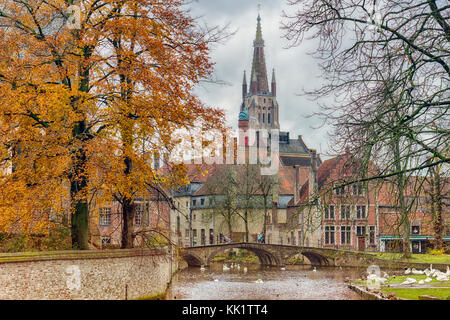Autumn view of The Beguinage bridge and Church of our Lady tower along the Bruges canal with swans - Stock Image