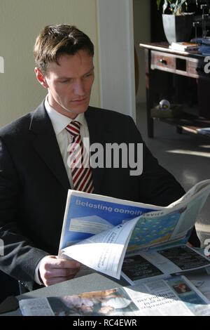 Over 30 caucasian business man in suit reading newspaper at the table  at home - Stock Image