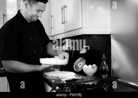 Handsome smiling male chef pressing pastry into a dish in a kitchen - Stock Image