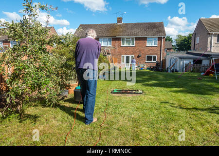 A man mows a lawn in a residential back garden with an electric lawnmower on a sunny day with blue sky in early summer. - Stock Image