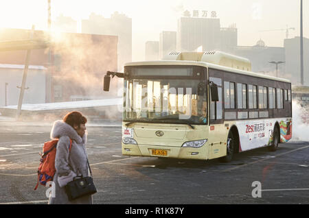 Woman passenger and public bus in parking area of Harbin West Railway Station - Stock Image