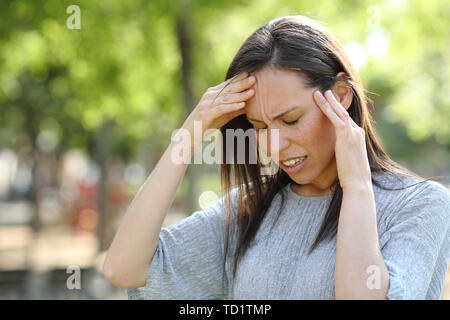Stressed woman suffering head ache standing outdoors in a park - Stock Image