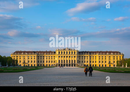 Palace Vienna, view at sunset of a middle age couple walking towards the south side of the Schloss Schönbrunn palace in Vienna, Austria. - Stock Image