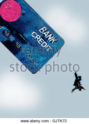 Businessman falling from large credit card - Stock Image