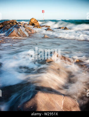 waves washing over rocks at the seaside - Stock Image