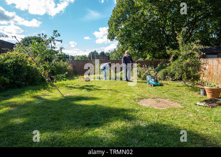 A retired couple doing gardening on a sunny day with blue sky in early summer. - Stock Image