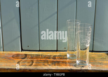 Two empty drinks glasses casting shadows - Stock Image