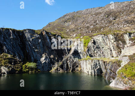 Steep sided flooded disused slate quarry pit on route to Carnedd Moel Siabod mountain in Snowdonia National Park. Capel Curig Conwy Wales UK Britain - Stock Image