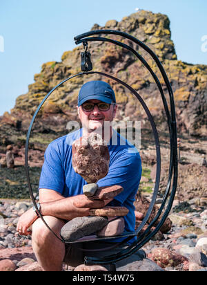 Dunbar, East Lothian, Scotland, UK. 21st Apr 2019. European stone stacking championship: Dave Love, from Edinburgh, balances stones at Eye Cave beach on the second day which comprises 2 competitions, a 3 hour artistic challenge and a children's competition. The overall winner receives a trip to llano Earth Art Festival & World Stone Balancing competition in Texas in 2020. Credit: Sally Anderson/Alamy Live News - Stock Image